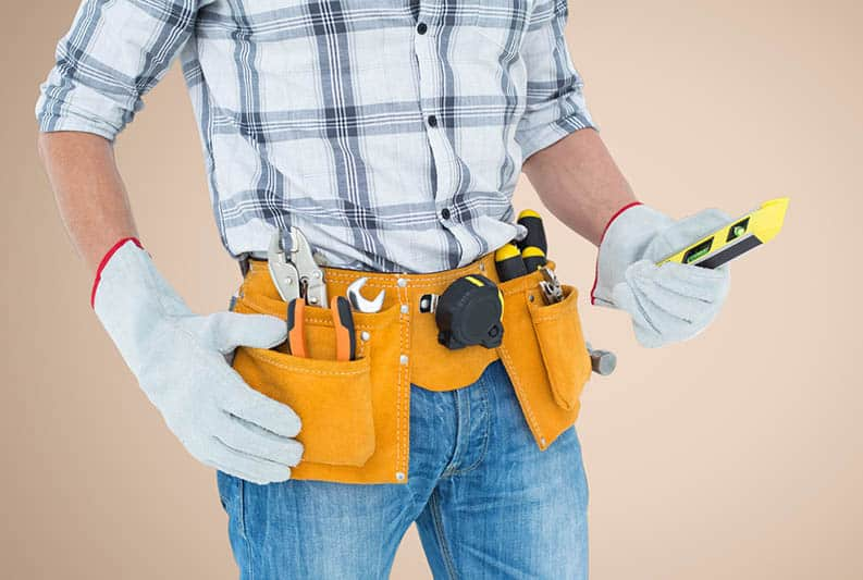 Mid-section of handy man with tool belt against cream background